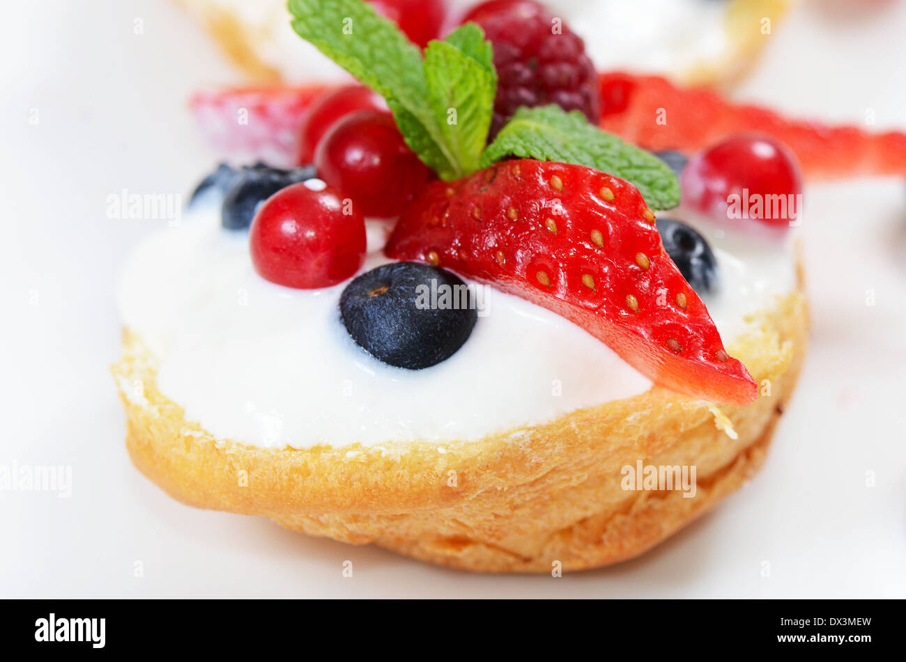 Profiteroles with berries currant strawberries and blueberries Stock Photo