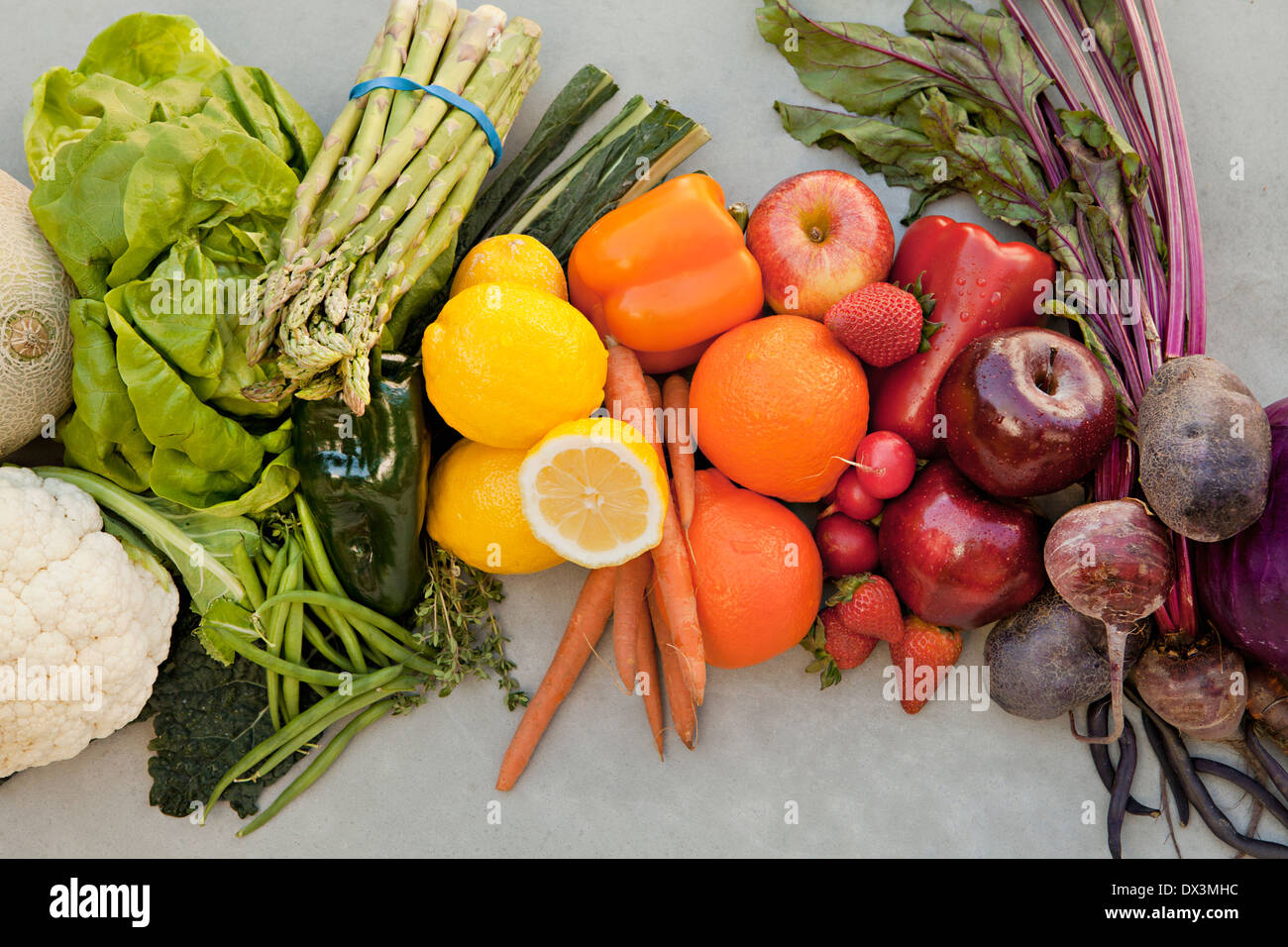 Abundant variety of multicolor fruits and vegetables organized by color on gray background, directly above - Stock Image