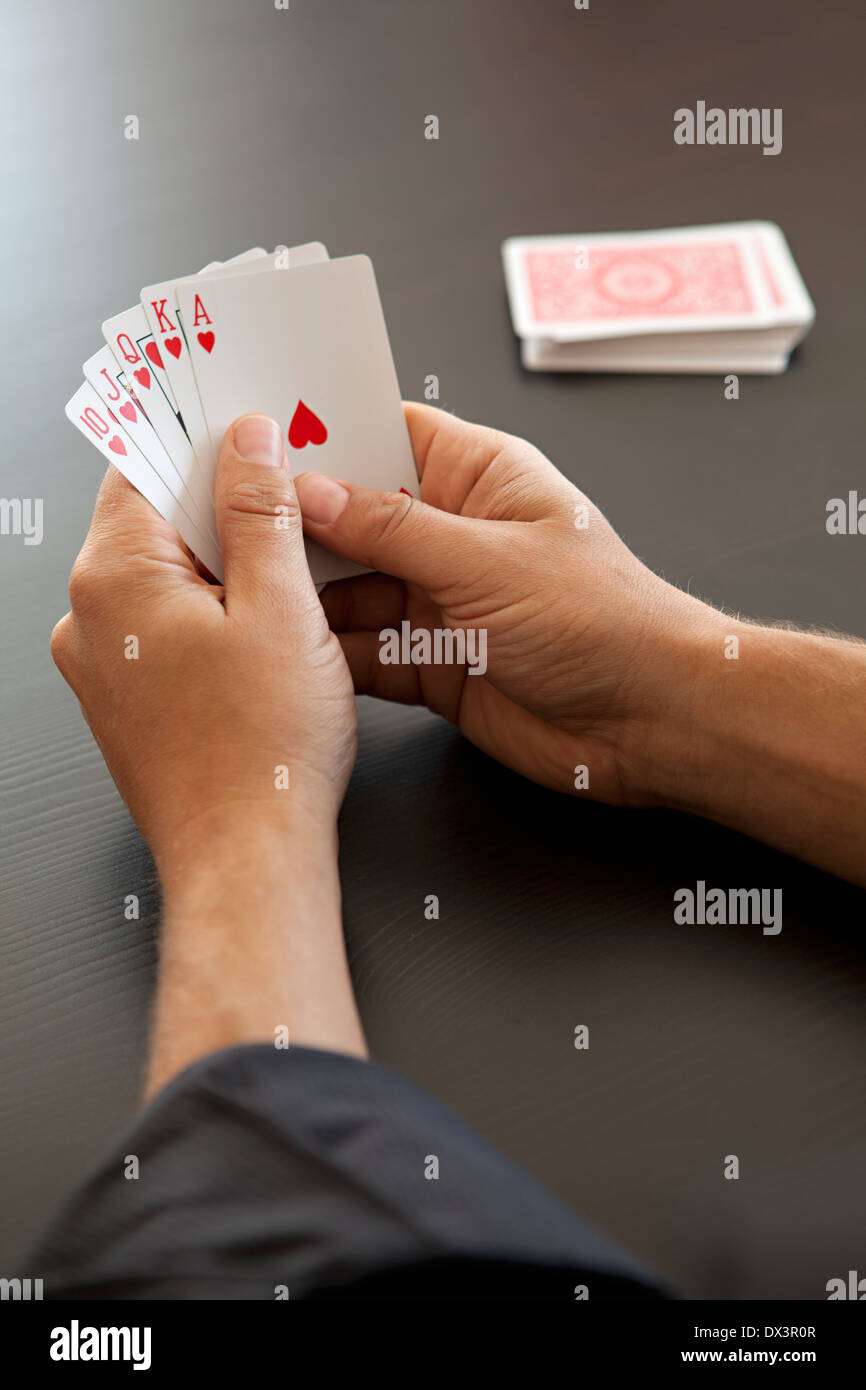 View of royal flush with hearts in hands of man playing poker with playing cards, high angle view - Stock Image