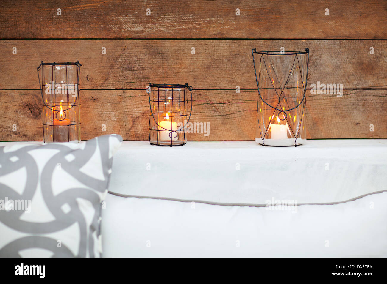 Candles illuminated in lanterns on patio ledge Stock Photo