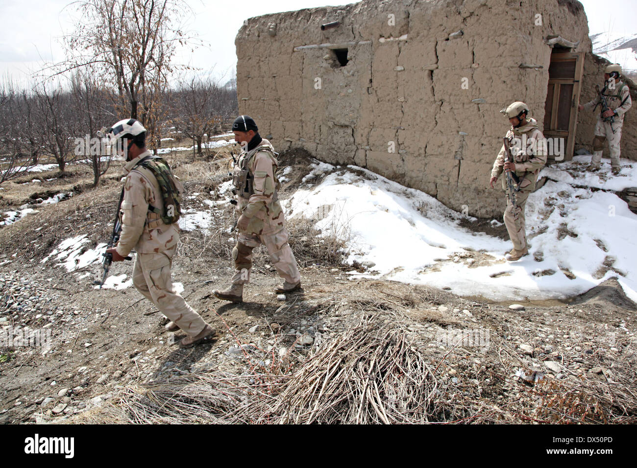 Afghan soldiers with Task Unit Wardak search a village during an armed reconnaissance operation March 6, 2014 in Zabodaq village, Wardak province, Afghanistan. - Stock Image