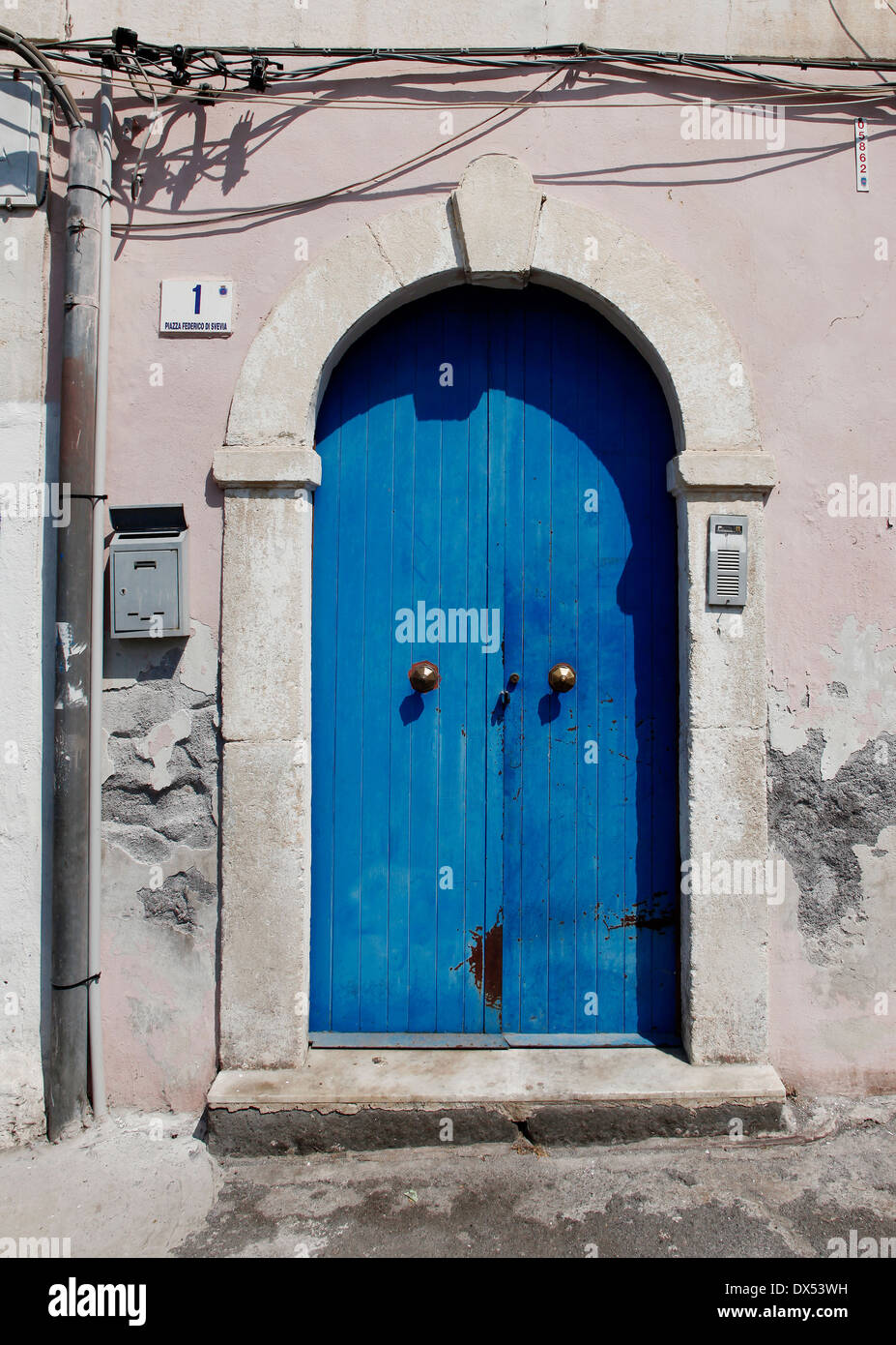 A blue door with mailbox, number 1 and entry phone - Stock Image