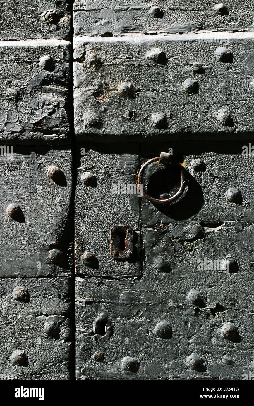A gray reinforced door with lock and handle - Stock Image