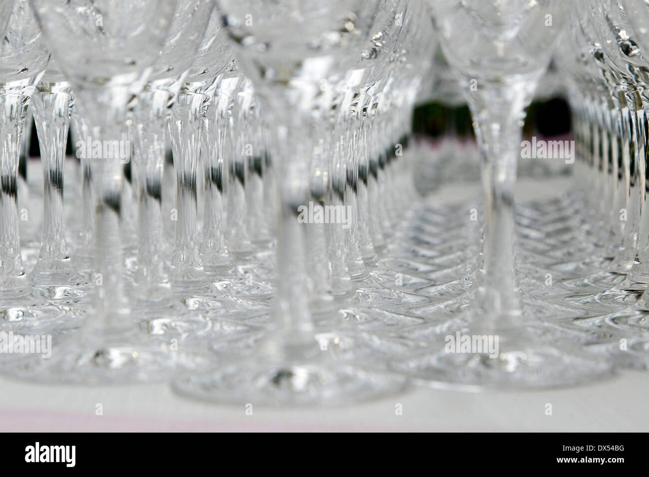 Wine glasses lined up on a table - Stock Image