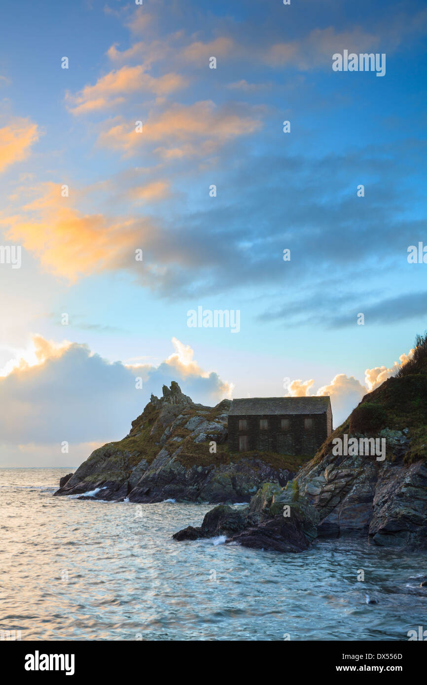 The Net Loft at the mouth of Polperro Harbour in Cornwall captured at sunrise - Stock Image