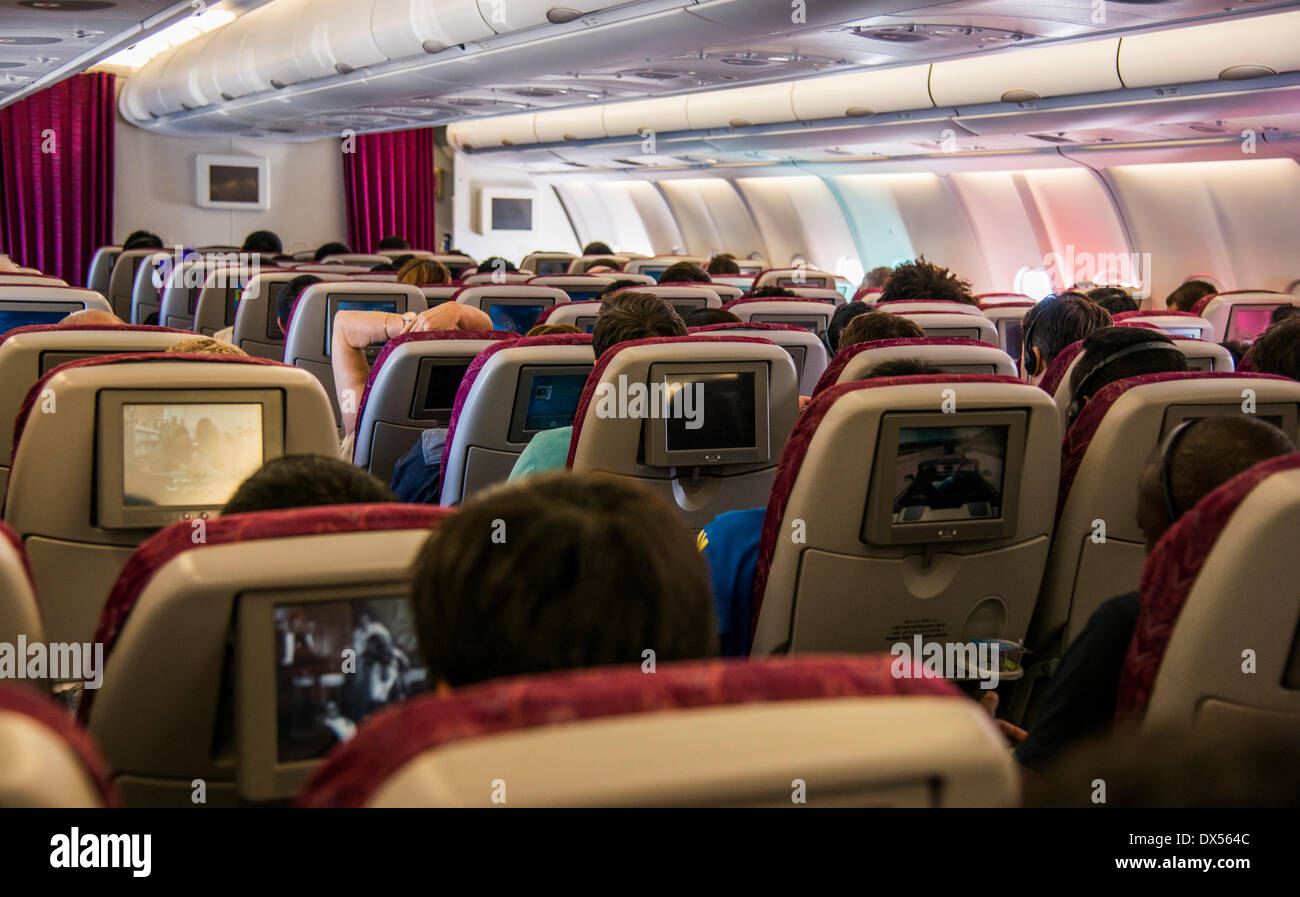 Cabin of a passenger aircraft with entertainment screens and passengers - Stock Image