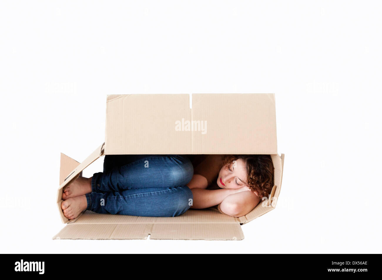 Young woman sleeping in a removal box - Stock Image
