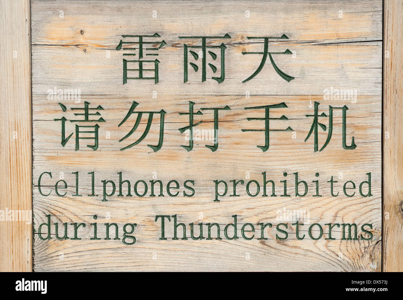Sign, with writing in Chinese and English 'cellphones prohibited during thunderstorms', Beijing, China - Stock Image