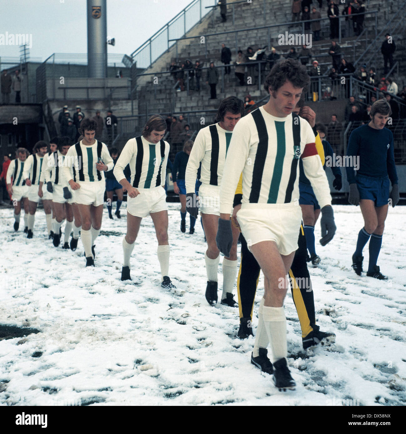 football, DFB Cup, 1973/1974, last sixteen, first leg, Stadium am Boekelberg, Borussia Moenchengladbach versus Hamburger SV 2:2 A.E.T., teams running-in, snow blanket, badly pitch conditions, f.l.t.r. the Gladbach players Rainer Bonhof, Henning Jensen, Ju - Stock Image