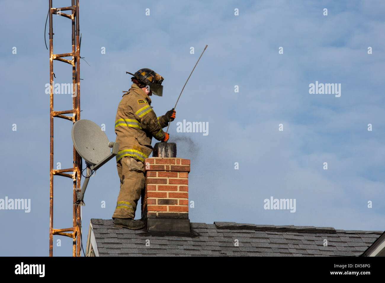 Kenton, Ohio - A firefighter fights a chimney fire in a rural house. - Stock Image
