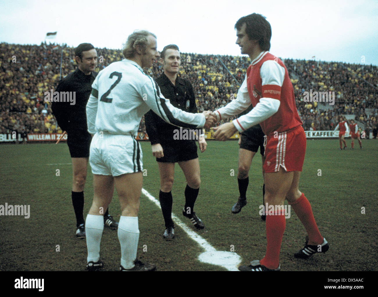 football, Bundesliga, 1974/1975, Stadium am Boekelberg, Borussia Moenchengladbach versus 1. FC Cologne 1:1, welcome, team captains Berti Vogts (MG) left and Wolfgang Overath (FC), behind referee Guenter Linn and assistants - Stock Image