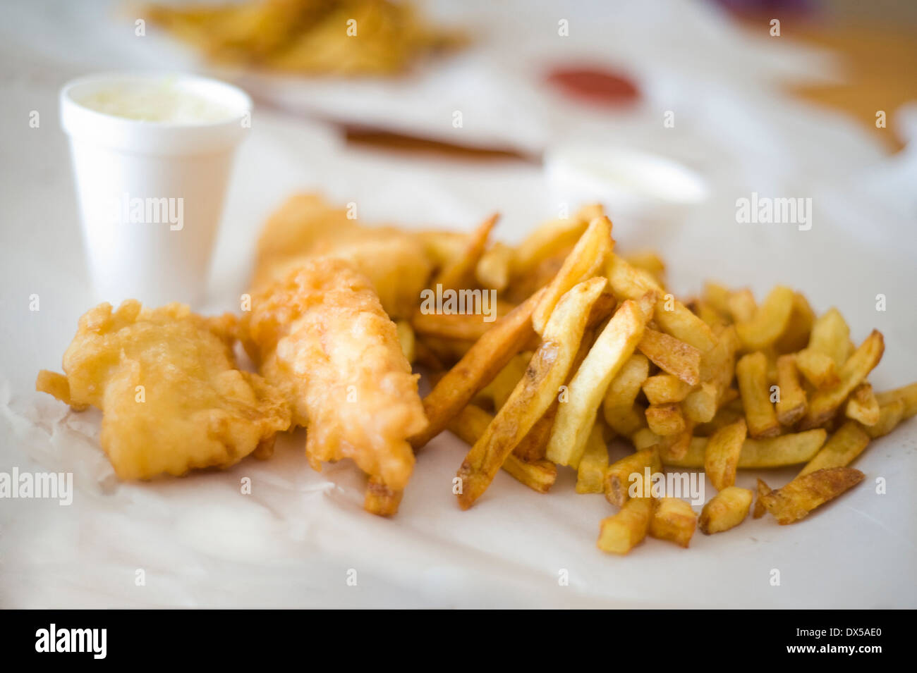 Take-out fish and chips on brown paper with a side of coleslaw in a styrofoam cup - Stock Image