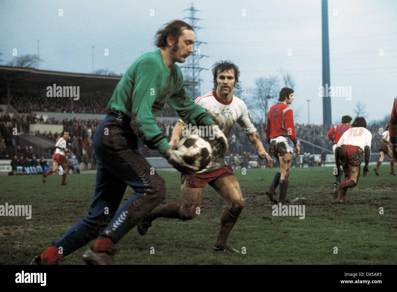football, 2. Bundesliga Nord, 1974/1975, Niederrheinstadion, Rot Weiss Oberhausen versus FC Bayer 05 Uerdingen 1:3, scene of the match, mudbath, goal kick of keeper Manfred Kroke (Bayer), behind Walter Krause (RWO) - Stock Image