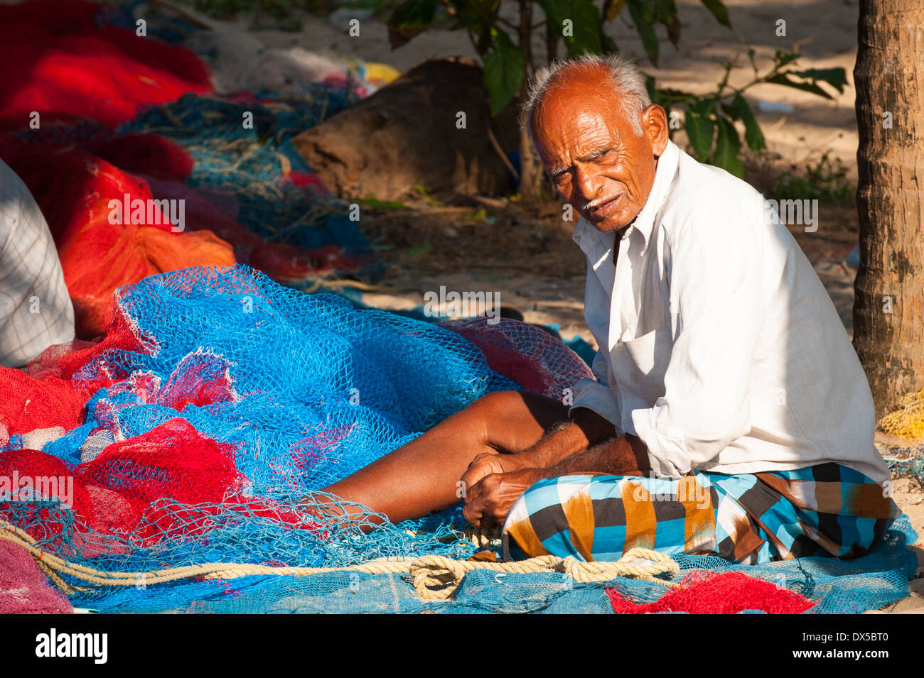 South Southern India Kerala Alleppy Mararikulam beach fisherman 0ld man male repairing mending net nets shore sand scene scenery - Stock Image