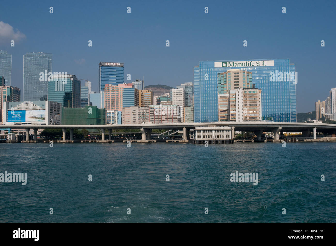 The small waterfront Kwun Tong ferry terminal is towerd over by the many high rise buildings in the area. - Stock Image