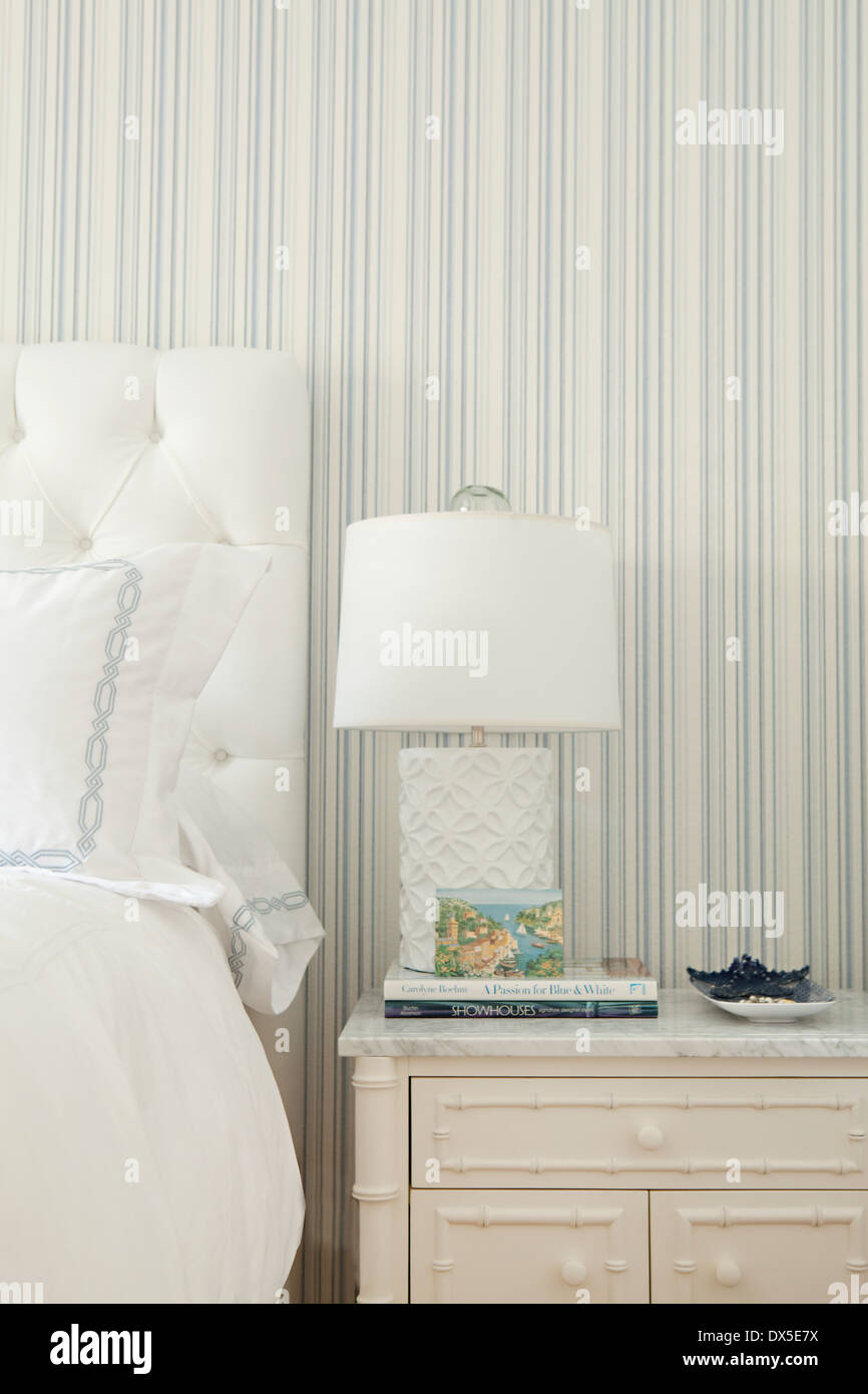 Bedside table with lamp in blue and white bedroom - Stock Image