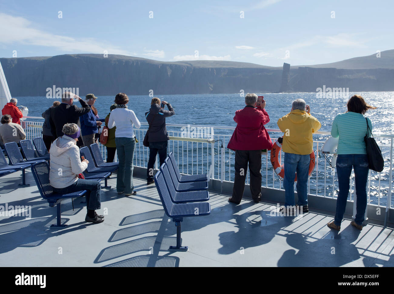 Passengers on MV Hamnavoe taking photographs of the Old Man of Hoy on the ferry trip from Scrabster to Stromness. - Stock Image