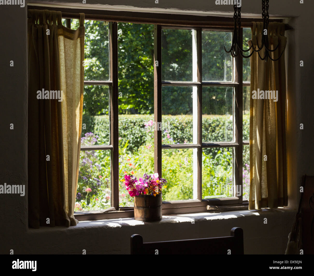 Cottage garden - View into a pretty country garden through a window in summer - Stock Image