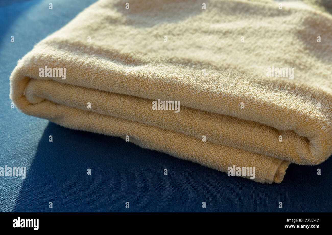 Towel folded on a bed - Stock Image