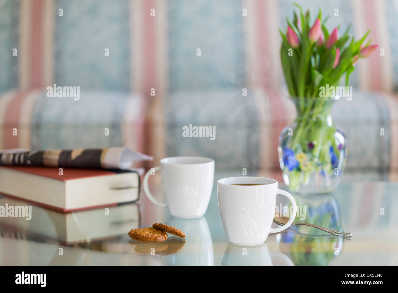 Coffee cups on glass table with spoon and ginger biscuits. Book and newspaper in the background - Stock Image