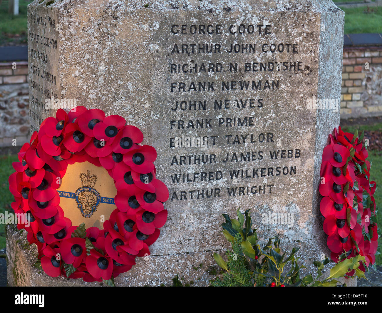 Poppy wreaths placed on war memorial to fallen First World War (World War I) soldiers by All Saints Church in Barrington, Cambridgeshire, England - Stock Image
