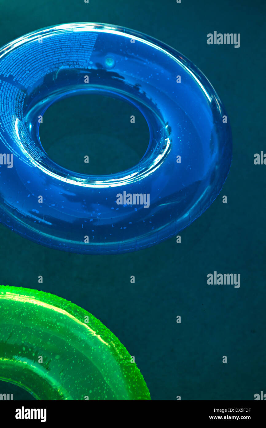 Blue and green inflatable rings in swimming pool, high angle view - Stock Image