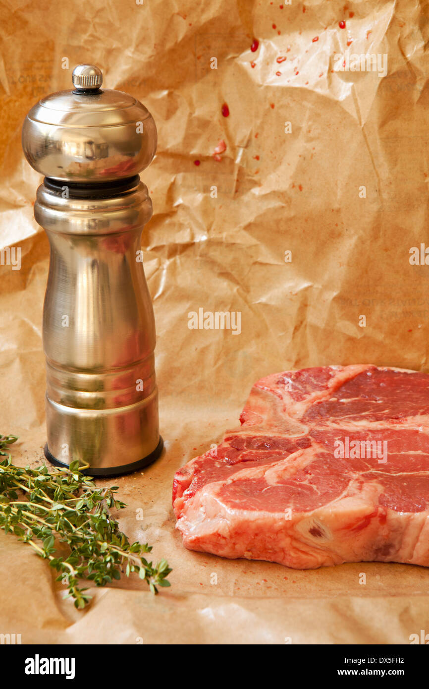 Raw meat with pepper mill and rosemary on butcher paper, close up - Stock Image
