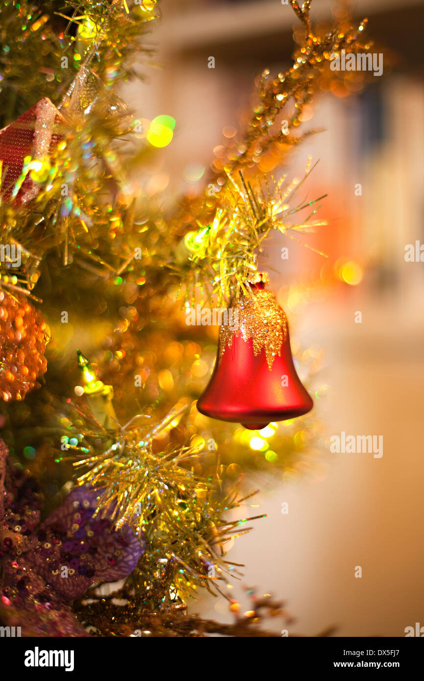 Red bell ornament hanging on Christmas tree, close up - Stock Image