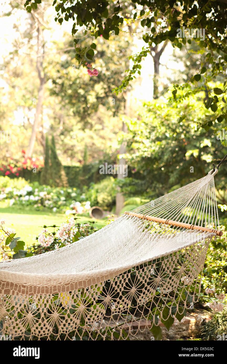 White lace hammock hanging from sunny idyllic lush garden - Stock Image