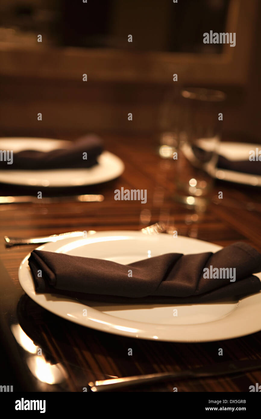 Black napkins at place settings on table, close up, tilt - Stock Image
