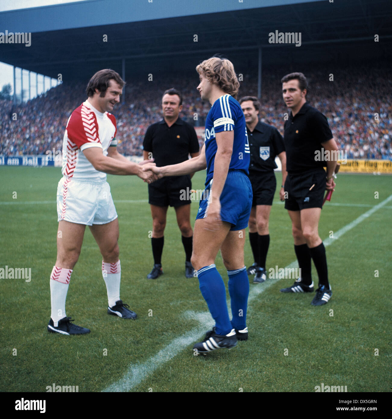 football, Bundesliga, 1975/1976, Georg Melches Stadium, Rot Weiss Essen versus FC Schalke 04 0:0, welcome of the team leaders Willi Lippens (RWE) left and Helmut Kremers (S04), behind referee Heinz Aldinger and assistants - Stock Image