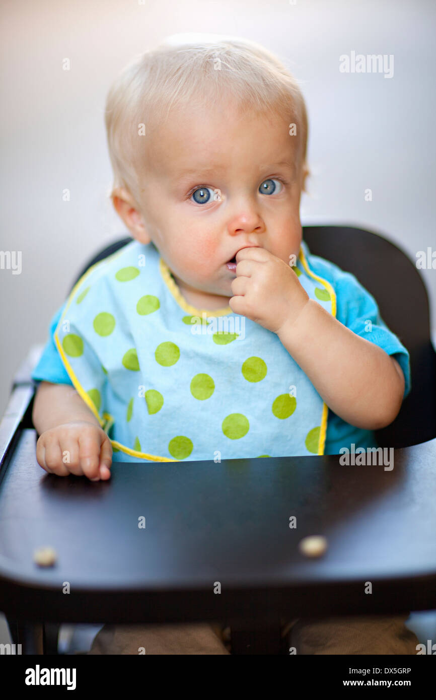 Wide-eyed, baby boy eating cereal in high chair with polka-dot bib, blonde hair, blue eyes, portrait - Stock Image