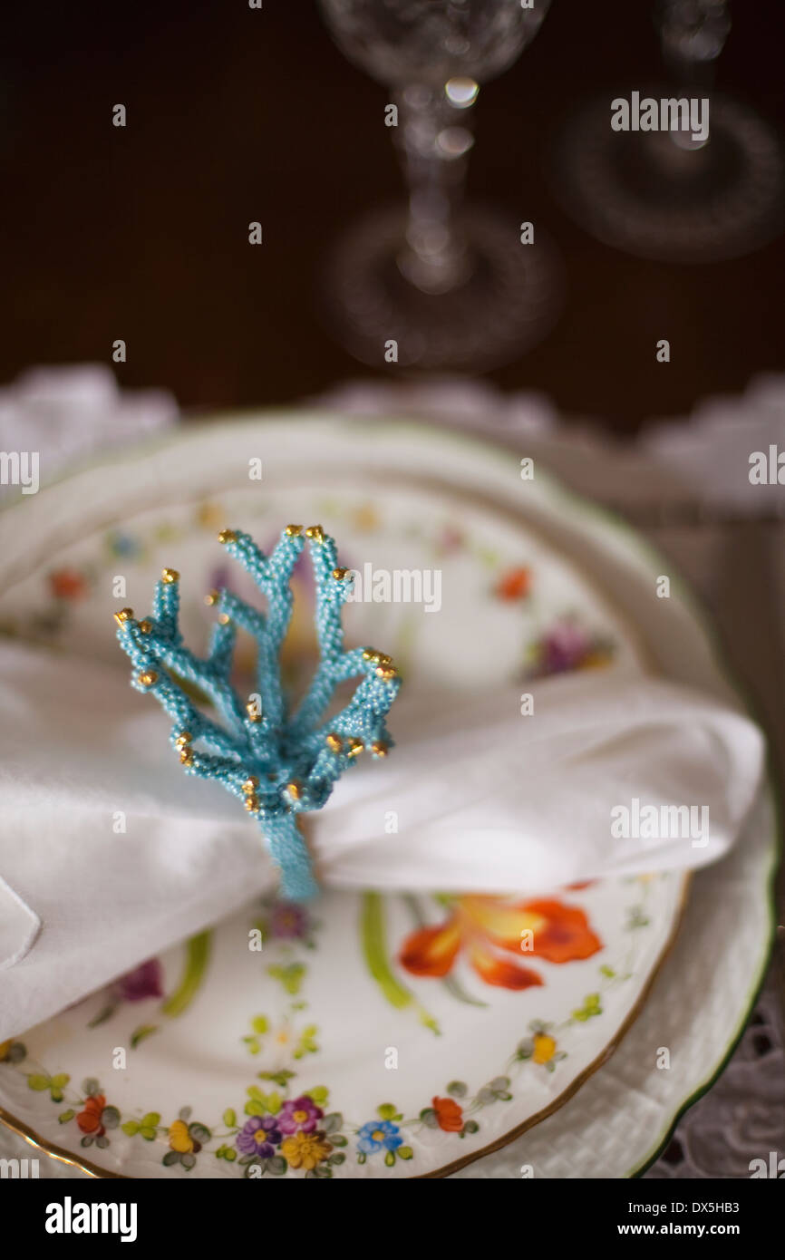 Blue coral napkin ring on floral plate, place setting, high angle view - Stock Image
