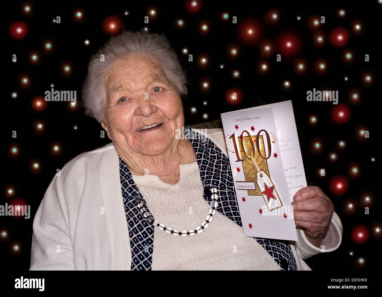 Happy alert elderly lady at 100 years of age holding a '100' congratulatory birthday card with 100 party lights behind - Stock Image