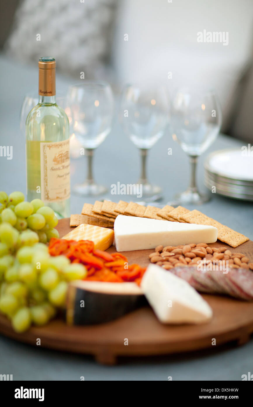 Cheese, crackers, nuts, grapes and salami on wooden cheeseboard next to white wine, close up Stock Photo