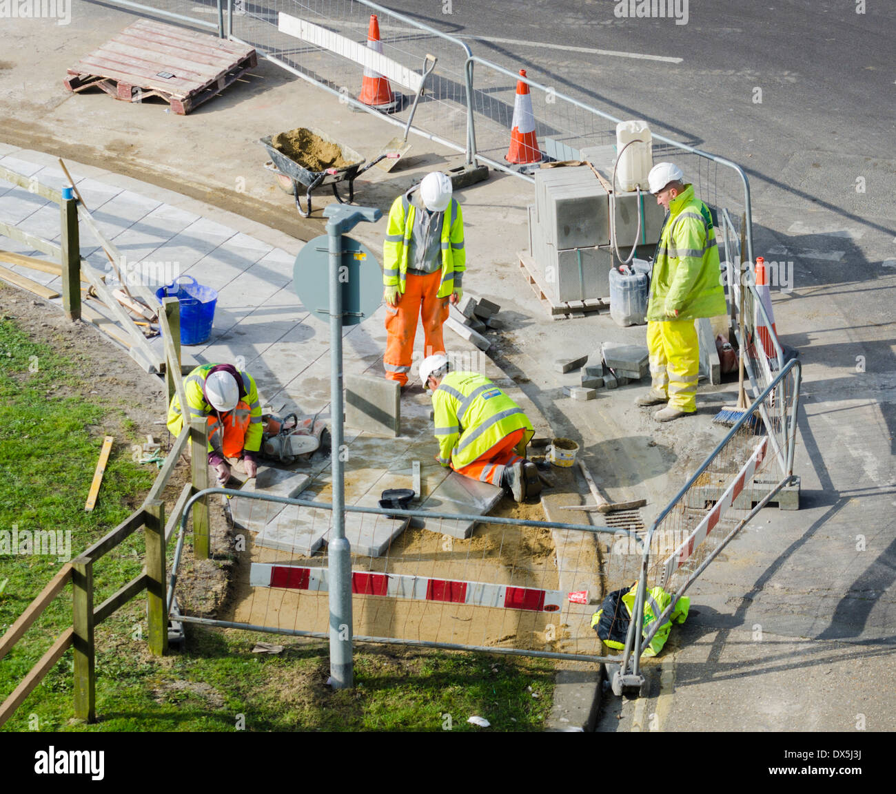 Workmen working by the road laying paving slabs in high visibility jackets. - Stock Image