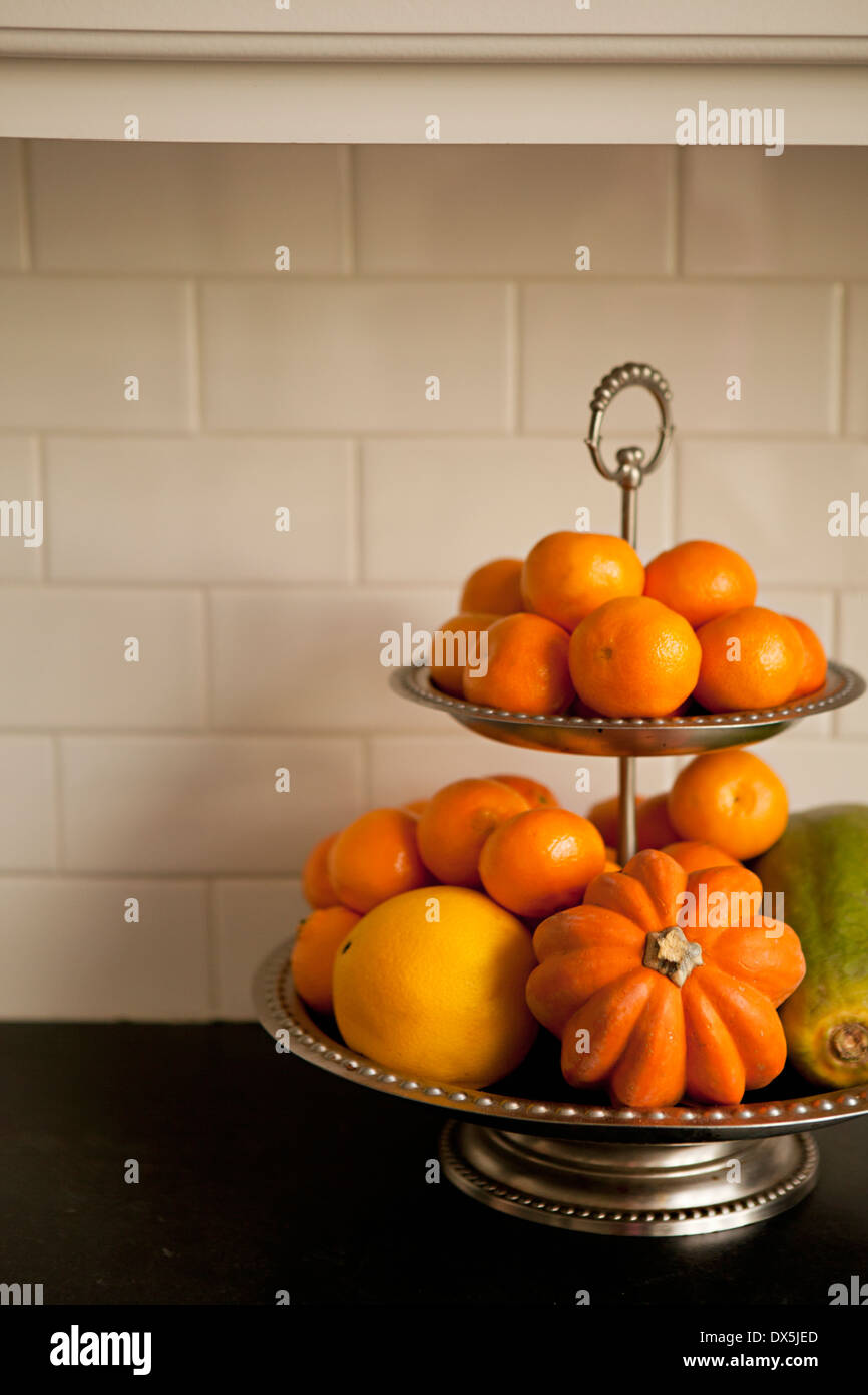 Tiered stand with orange fruits and vegetables on domestic kitchen counter, close up - Stock Image