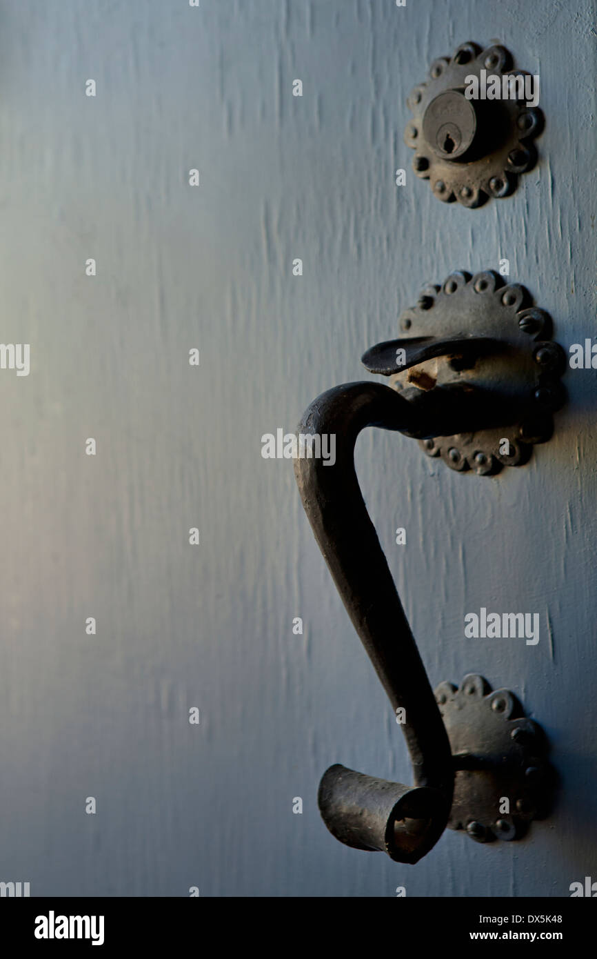 Ornate iron handle detail on blue door, close up - Stock Image