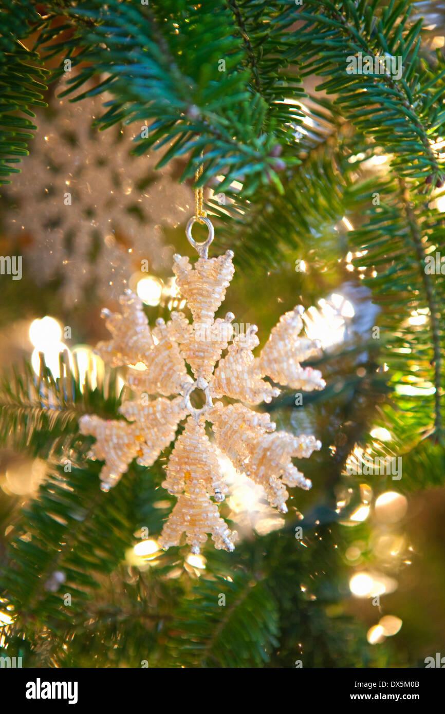 Snowflake ornament hanging on illuminated Christmas tree, close up - Stock Image