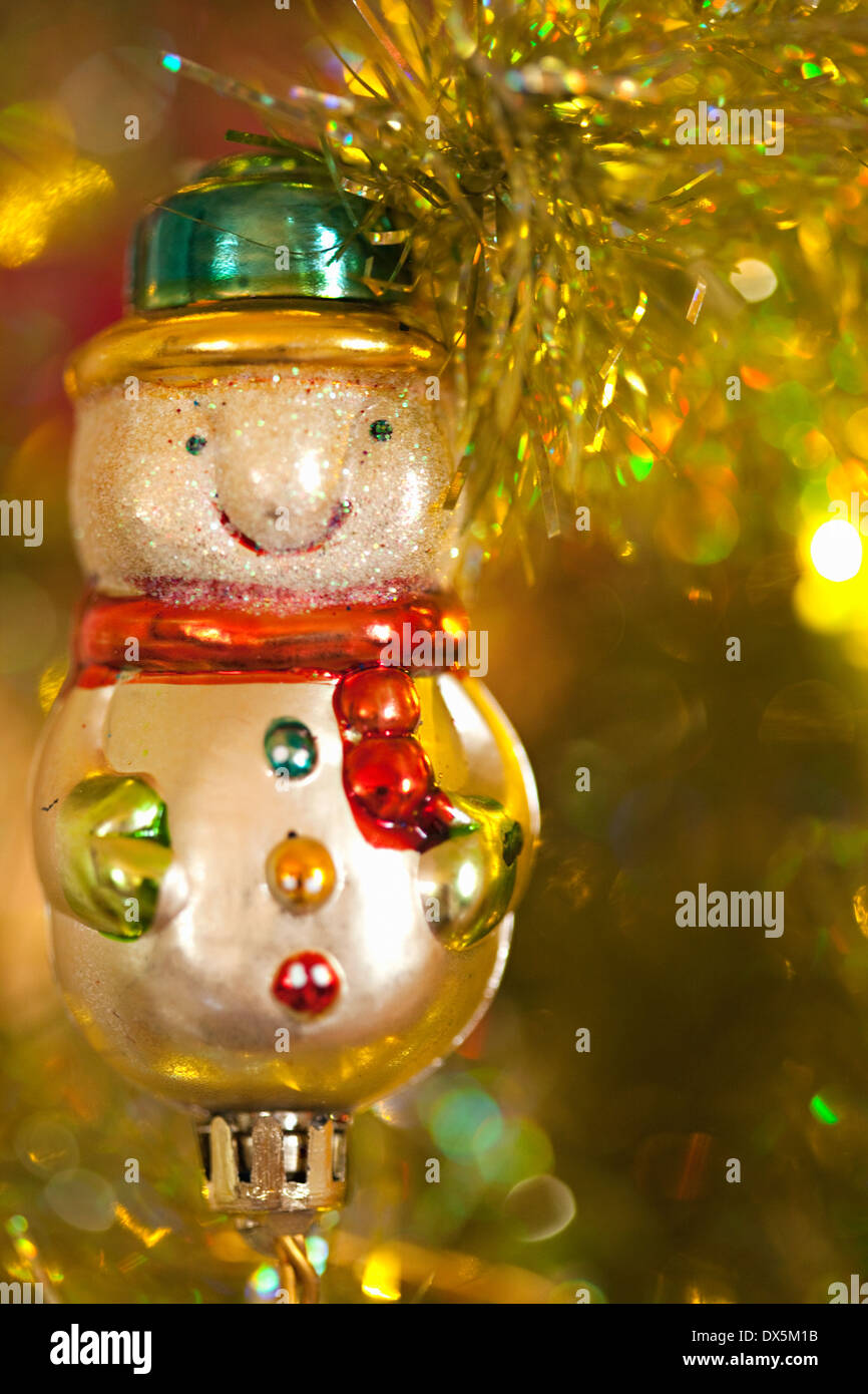 Snowman ornament hanging on illuminated Christmas tree, close up Stock Photo