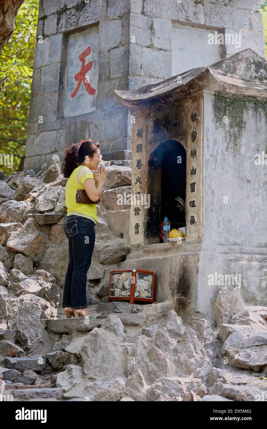 A young woman prays at a Buddhist shrine near Ngoc Son Temple, Hanoi, Vietnam,  South East Asia - Stock Image