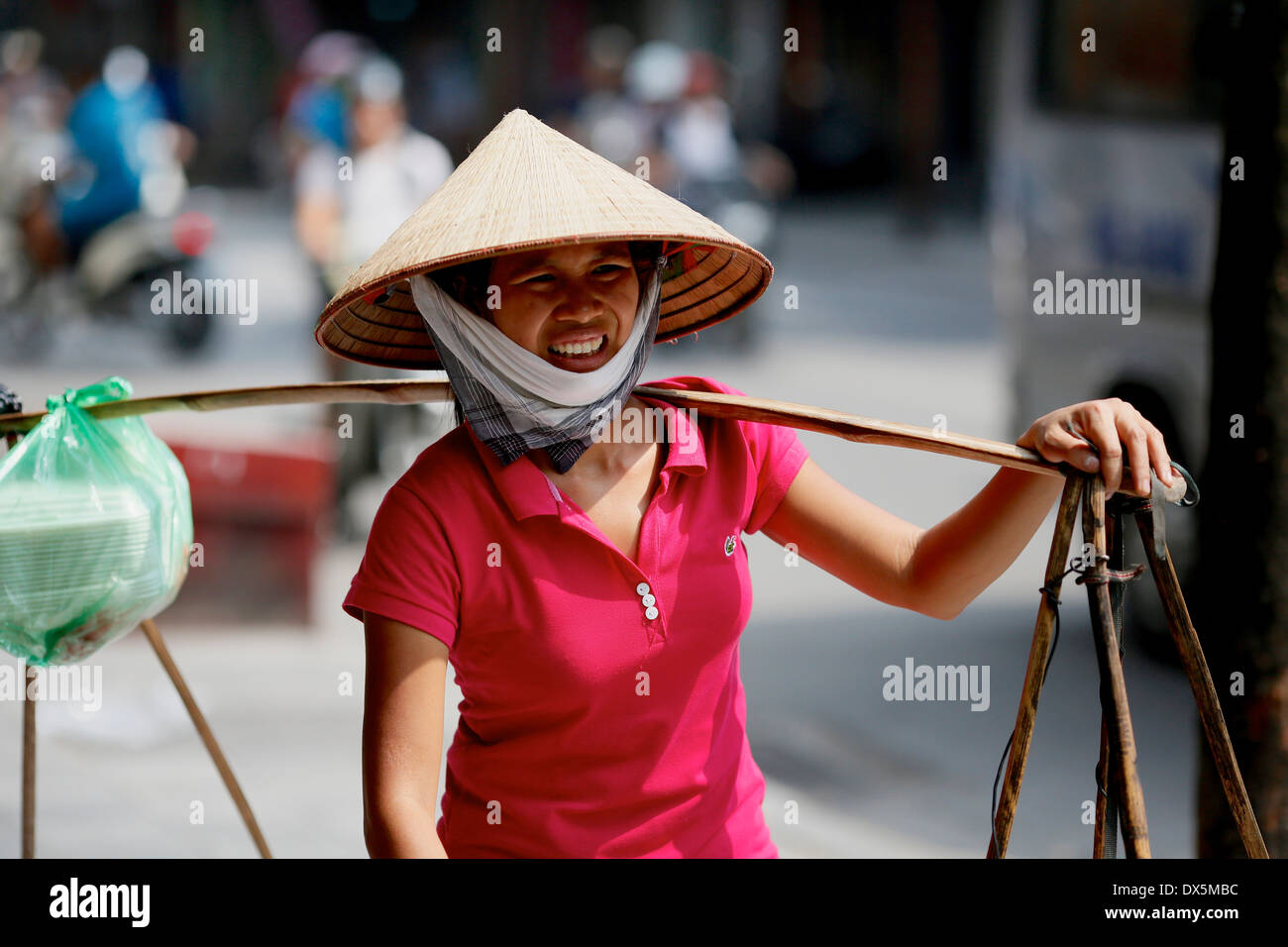 Street scene in the old quarter of Hanoi.  Street trader  in traditional conical hat carrying food using a traditional yoke. - Stock Image