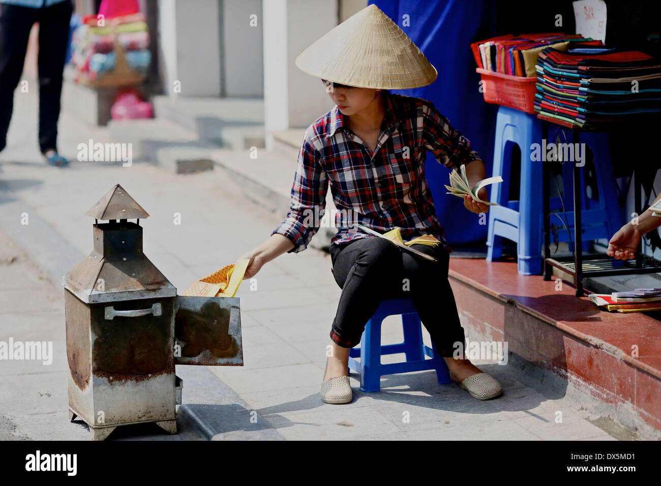 A shopkeeper in Hanoi's old quarter burns  fake money as an offering to the ancestors. Hanoi Vietnam South West Asia - Stock Image