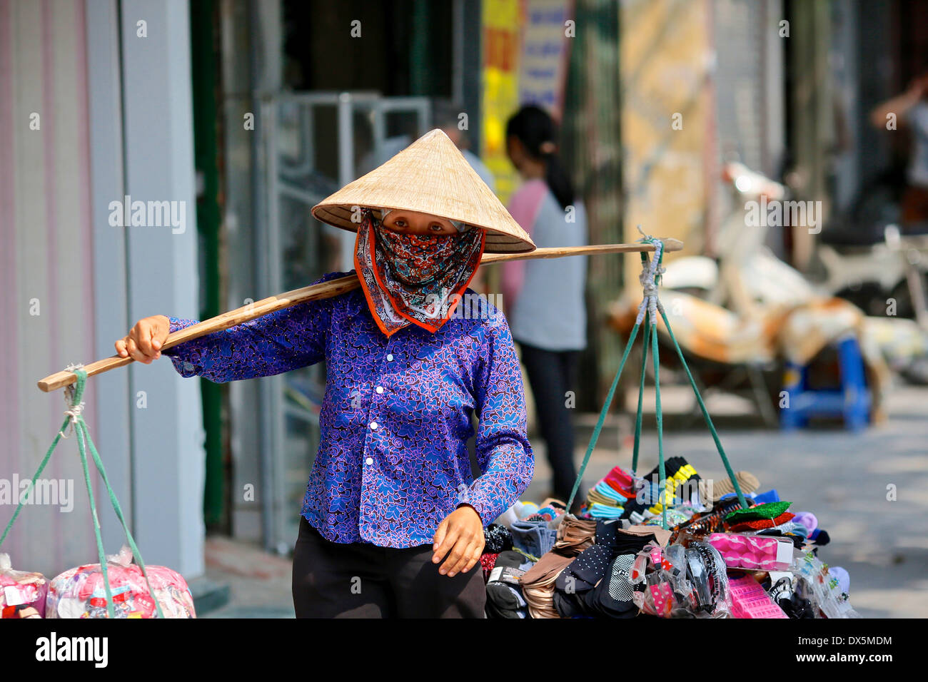 Street scene in the old quarter of Hanoi.  Street trader  in traditional conical hat carrying goods using a traditional yoke. - Stock Image