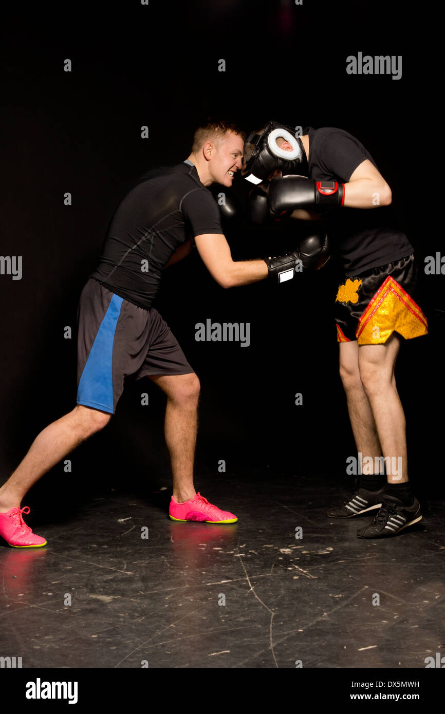 Two young boxers sparring in the ring during a training session as the one goes in for a low blow punch to his opponents Stock Photo