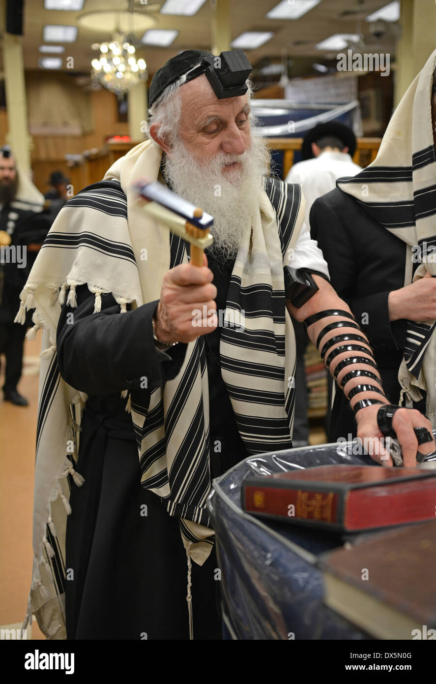 A religious Jewish man turning his noisemaker grogger at the mention of Haman during the reading of the Megillah on Purim in NYC - Stock Image