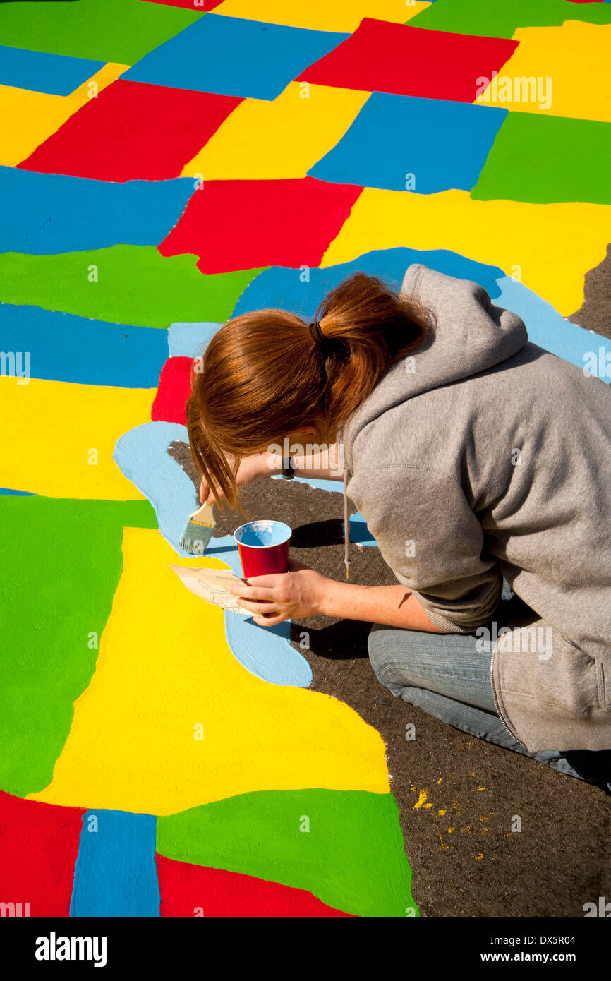 A young adult volunteer artist paints the Great Lakes on a map of the United States on an elementary school playground in Garden Grove, CA. - Stock Image