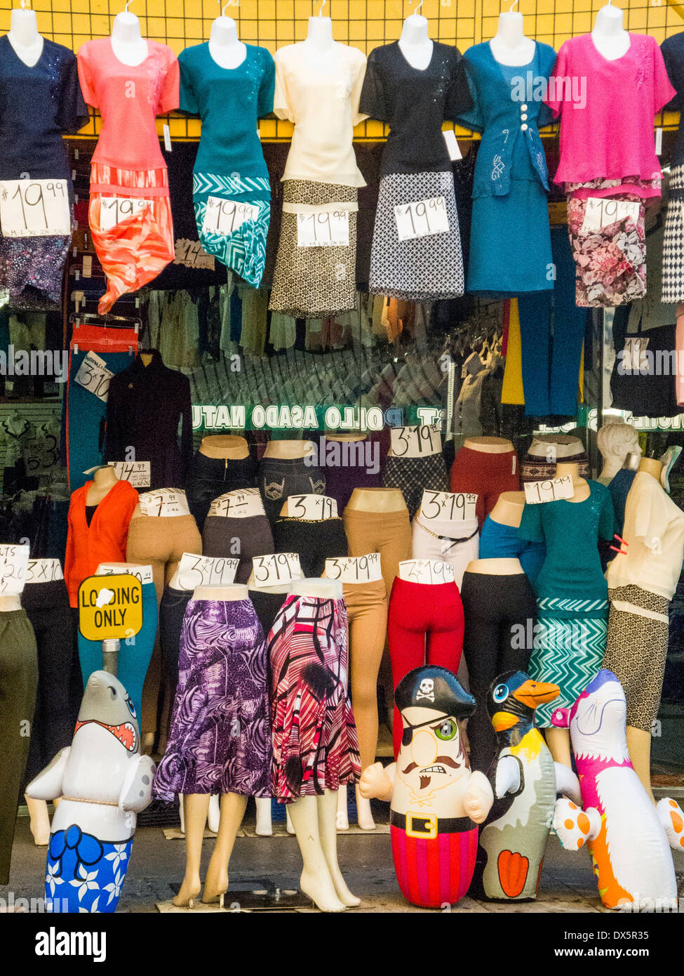 Displayed on partial body mannequins, a sidewalk clothing sale in the Los Angeles garment district has a surrealist look. Note hand written price tags. - Stock Image