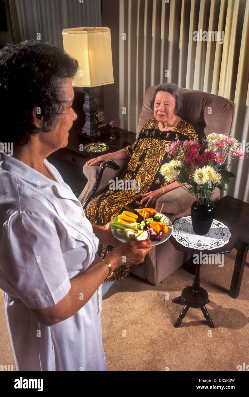 A uniformed Hispanic home healthcare worker serves food to an elderly woman client in Laguna Niguel, CA. Note fresh flowers. - Stock Image