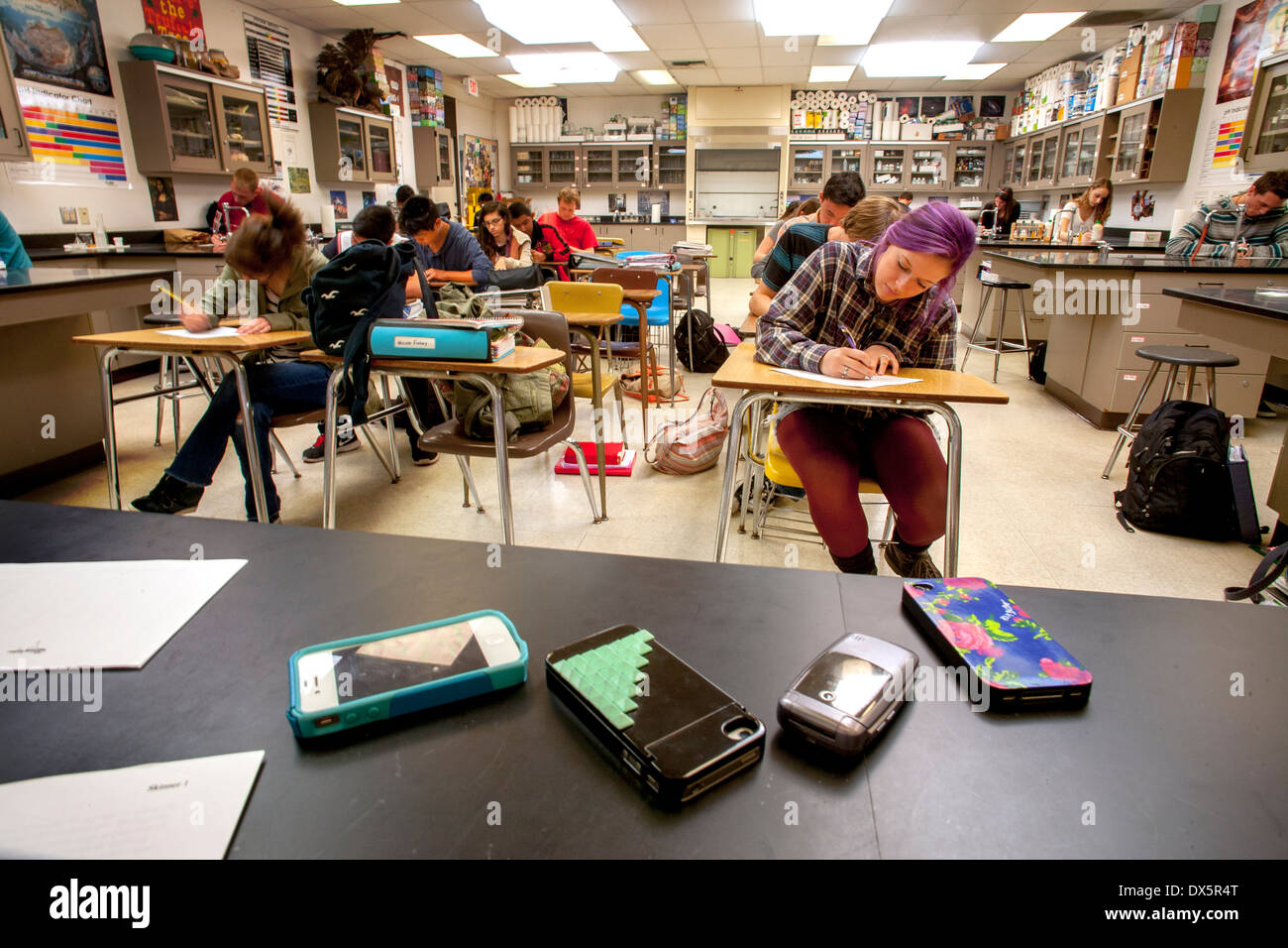 Teen high school chemistry students place their cell phones on the teacher's desk to avoid distraction while taking a classroom examination in San Clemente, CA. - Stock Image